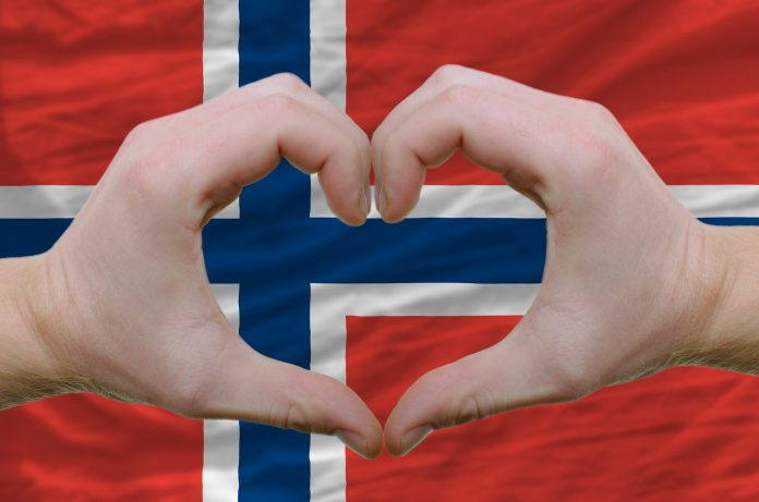 The Norwegian flag and two hands shaped as a heart. | Copyright: vepar5 - fotolia.