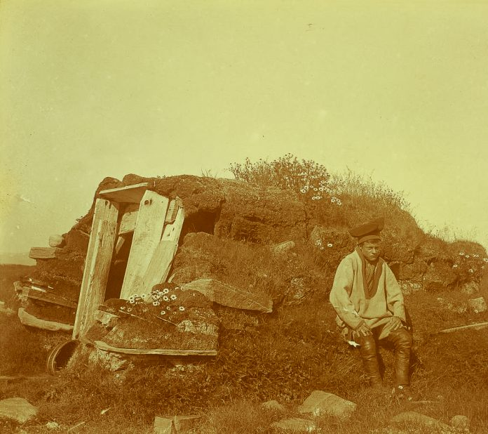 A Sami man sitting in front of a well on Tamsøya, an island off the coast of Finnmark, Norway. Possibly taken in 1903. | Photo: Robert Collett - nb.no - Public domain.