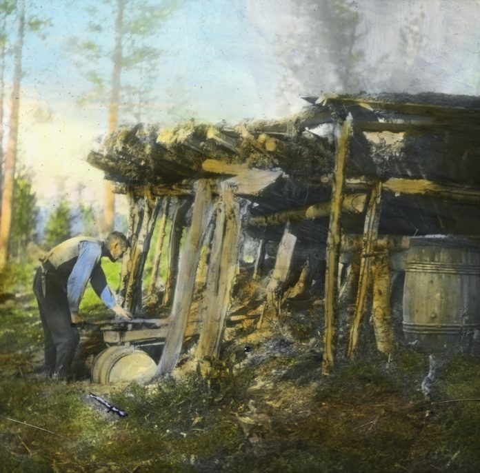 A man is making tar by burning resin-rich pine wood. The tar was used to preserve the wood in boats and buildings - and to preserve rope and fishing nets. Hand-coloured photo - taken in Målselv, Troms, Norway in 1928. | Photo: Anders Beer Wilse - digitaltmuseum.no DEX_W_00089 - cc by.
