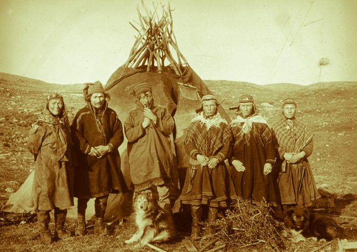 Henrik Sara, his wife, two daughters and a third girl outside their tent. Mikkel Bonga with the pipe. Cedar's mine, Badderen, Kvænangen, Troms, Norway. | Photo: Hanna Resvoll-Holmsen - digitaltmuseum.no FBib.01005-070 - Public domain.