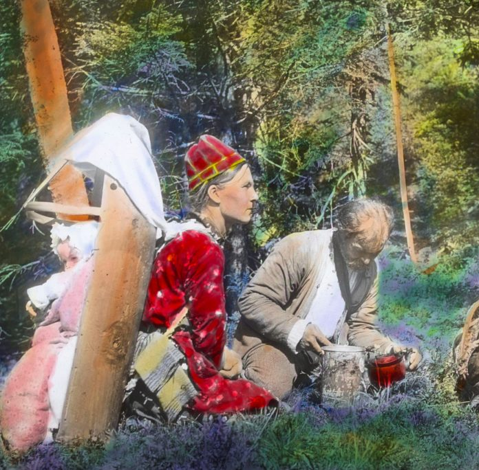 Coffee-break by the fire. Peder Vesterfjell and his family. Vefsn, Nordland, Norway. Hand-coloured photo. | Photo: Alf Schrøder co - digitaltmuseum.no FBib.01005-077 - Public domain.
