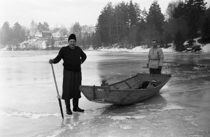 Two men are crossing the ice with an ice pick and a boat for safety. Every year, people go through the ice and perish. Our recommendation is never to venture out onto an icy lake, pond or river - unless you are with someone knowledgeable and local. The location is Lake Totak in Vinje, Telemark, Norway. | Photo: Unknown - digitaltmuseum.no NVE_Iskontorets_negativruller00007 - cc by-sa.