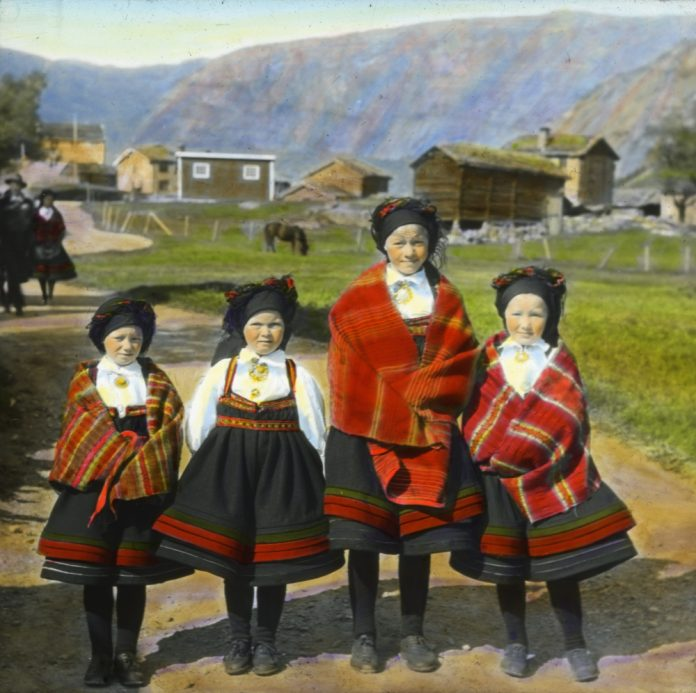 On their way to church. Four girls in their folk costumes from Setesdal. The photo is hand-coloured and taken in 1934 - somewhere in Aust-Agder, Norway.   Photo: Anders Beer Wilse - digitaltmuseum.no DEX_W_00067 - cc by.