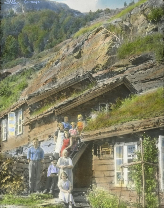 The location is the Åkernes mountain farm, Stranda, Geiranger, Møre og Romsdal, Norway. The photo is hand-coloured and taken in 1937. | Photo: Anders Beer Wilse - digitaltmuseum.no DEX_W_00050 - cc-by.