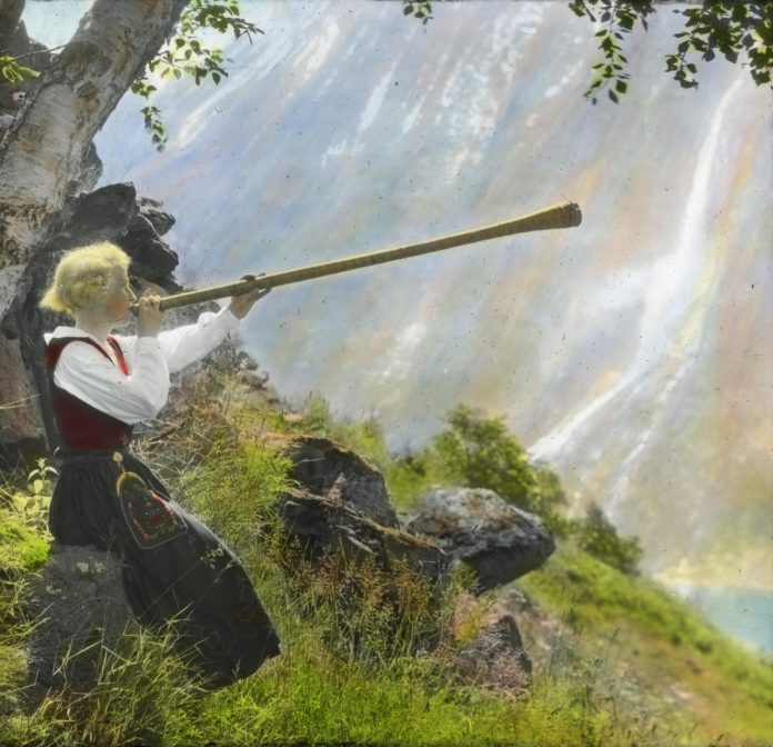 Anna Vinje about to play her «lur» - a shepherd's horn. The location is Geiranger, Stranda, Møre og Romsdal, Norway. Hand-coloured photo taken in 1935. | Photo: Anders Beer Wilse - digitaltmuseum.no DEX_W_00051 - cc by.